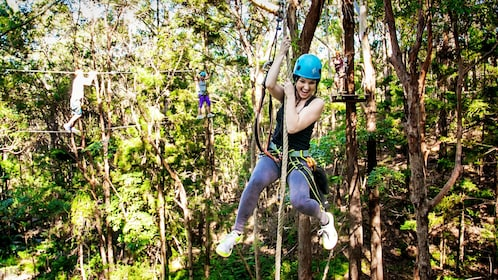 Woman hanging onto a rope in the trees in Australia