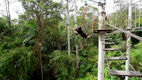 Man jumping while tethered to a wooden bridge in Australia