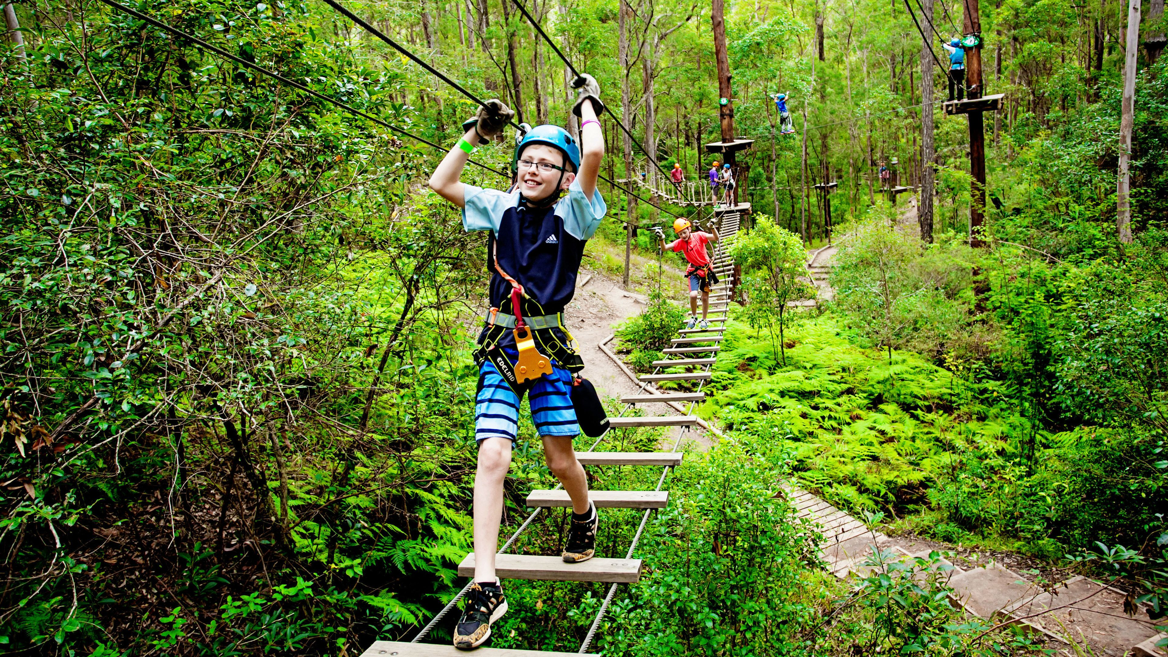 Boy walking a rope bridge in the trees in Australia