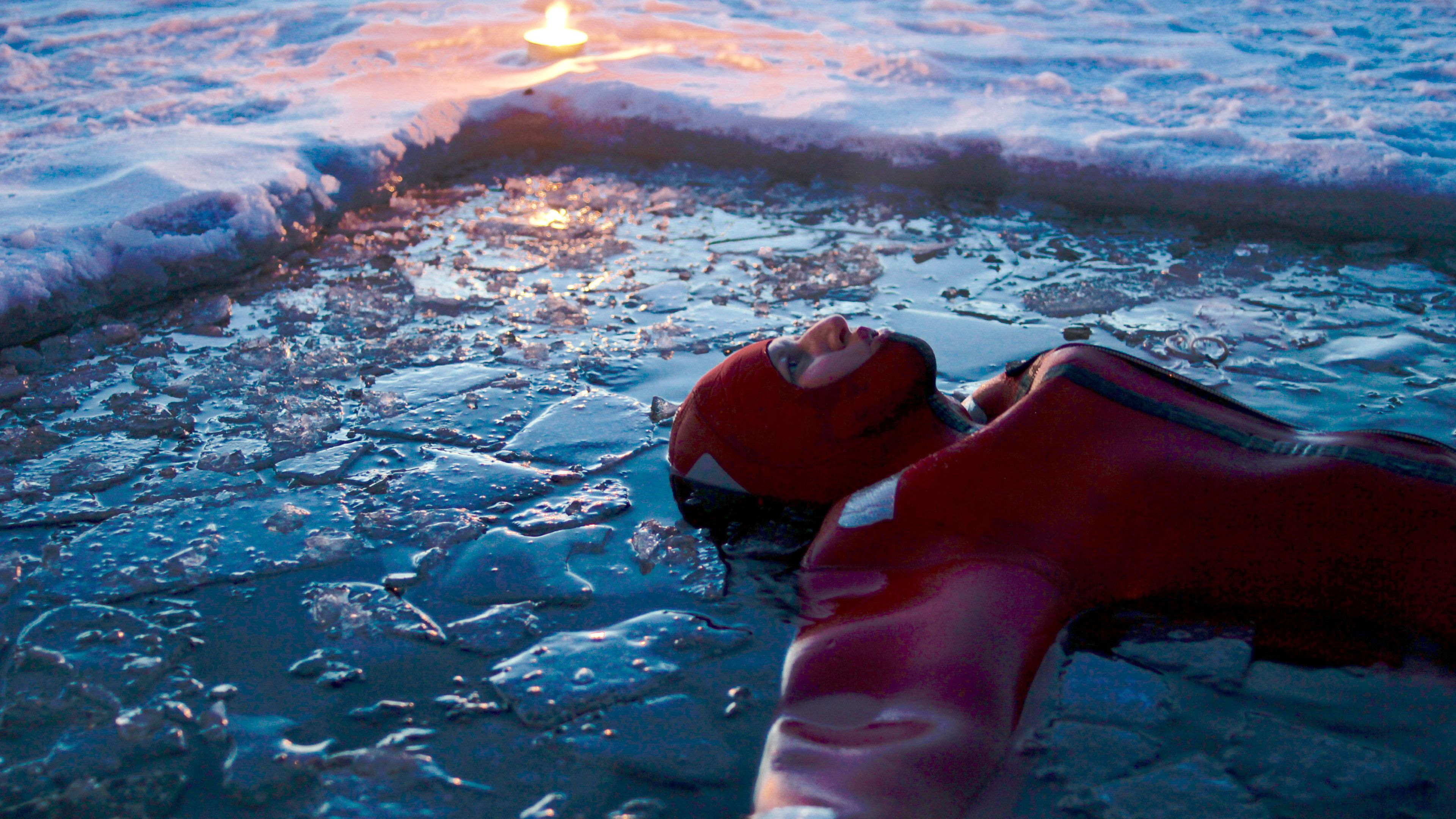 Person floating in an ice pool at dusk in Lapland