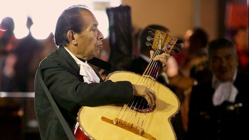 Mariachi musician playing a large guitar
