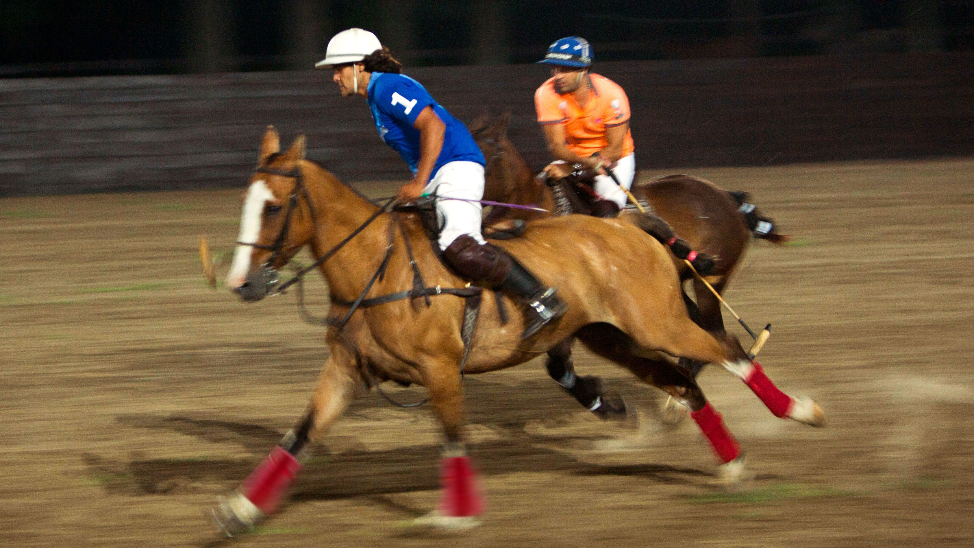 Two people on horseback playing Polo at night in Buenos Aires