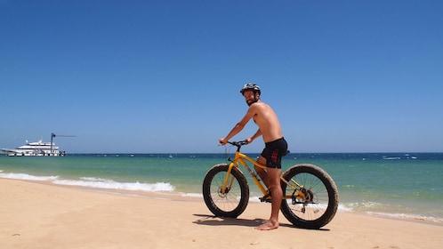 Man on fat tire bike rides down beach on Moreton Island