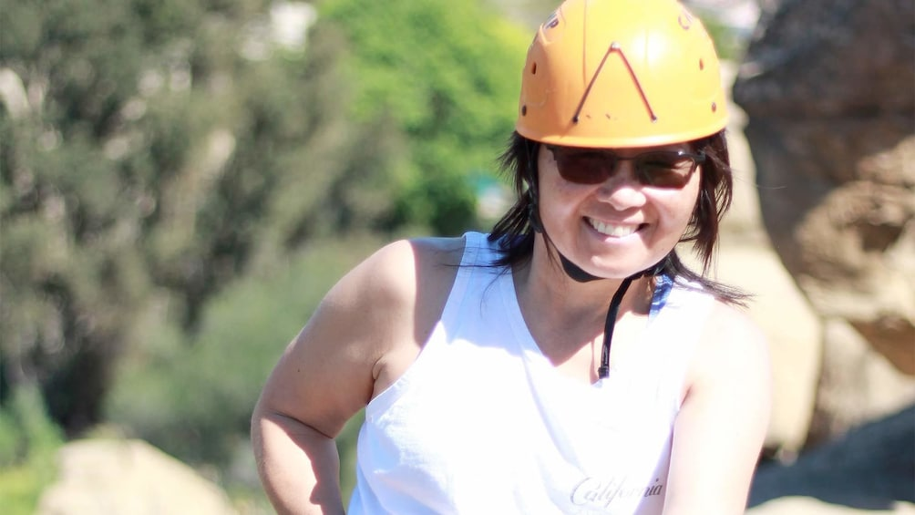 Show item 3 of 4. Woman wearing a safety helmet and smiling on the Rappelling Adventure at Joshua Tree