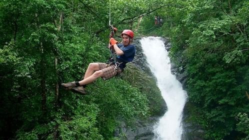 Man ziplining over a waterfall in Costa Rica