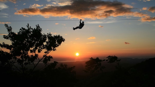 Silhouette of a zipliner at sunset in Costa Rica