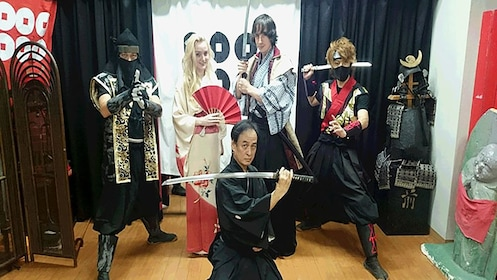People posing in traditional Japanese clothing for photograph with swords in Osaka