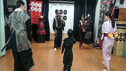 People in traditional Japanese clothing with swords in studio in Osaka