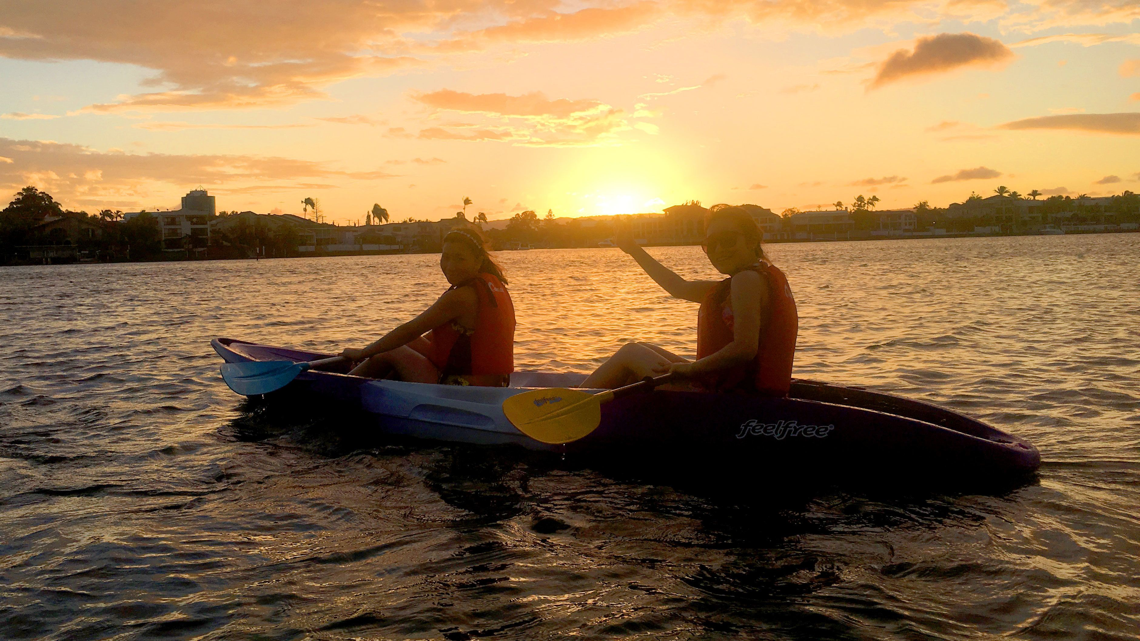 Two people in a kayak at sunset