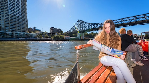 A woman reading on a riverboat in Brisbane