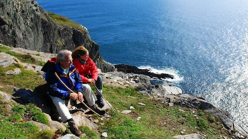 Couple sits on a cliff in Ireland