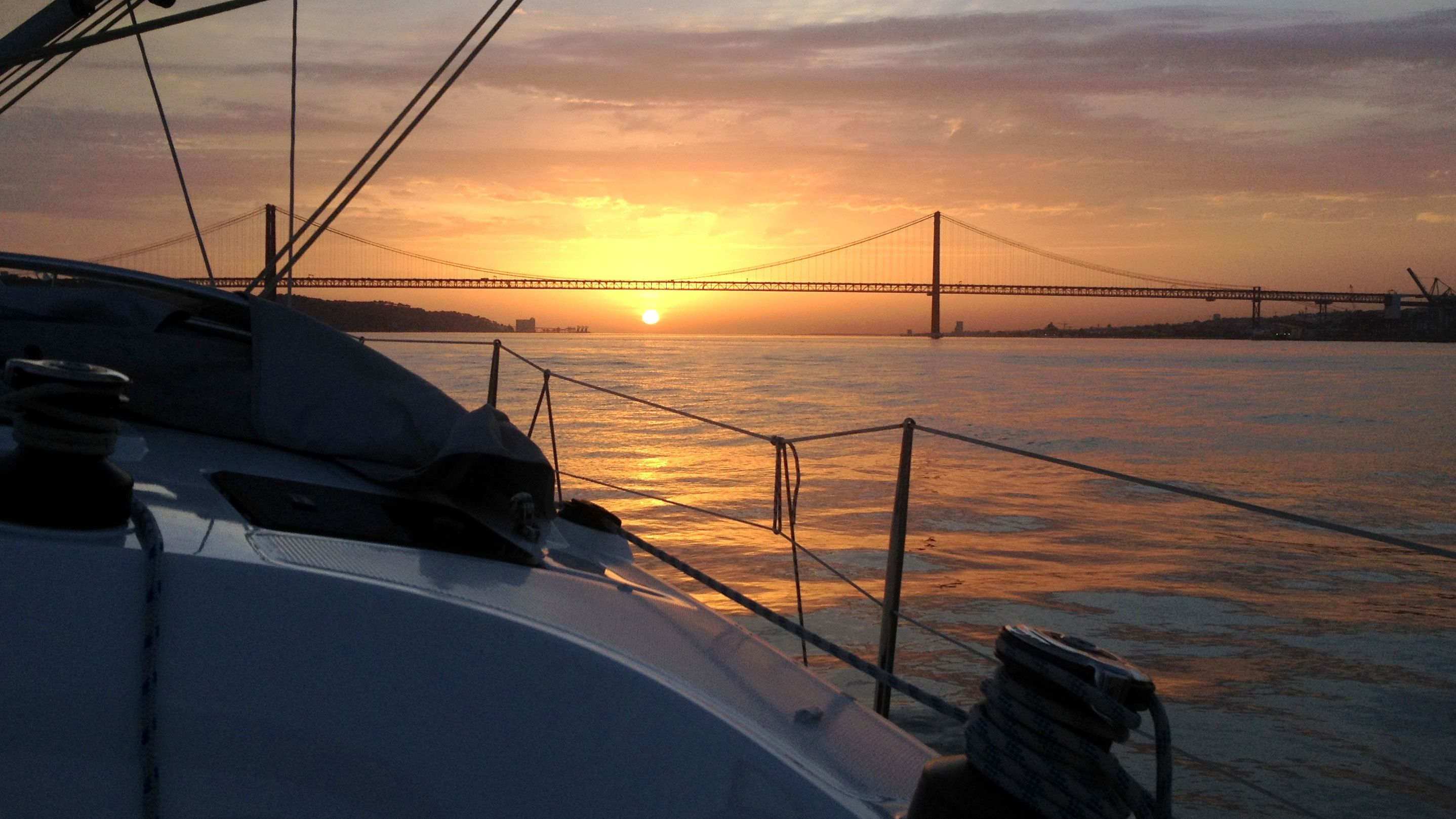 Sunset over bow of boat in Lisbon