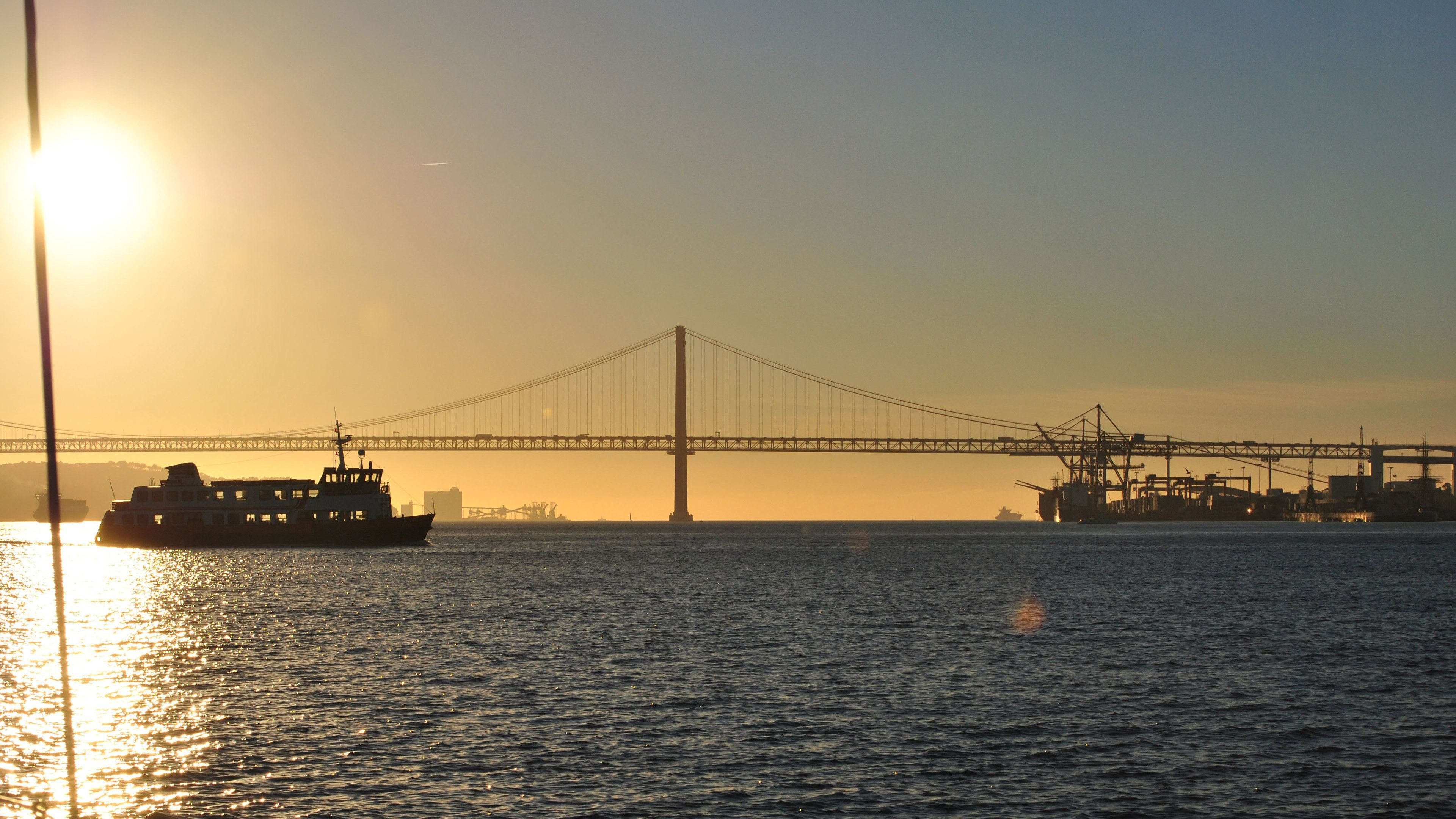 View of bridge and ferry in Lisbon at sunset