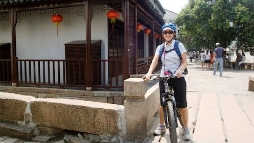 Woman on a bike tour at a temple in Shanghai