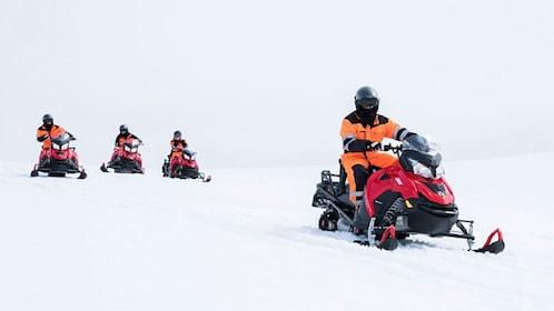 Snowmobile group riding through snow