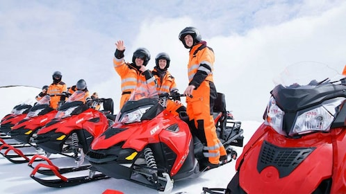 People sit on snowmobiles in Iceland