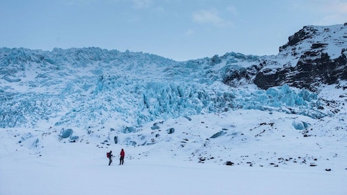 Two people hiking on a snow covered Mountain top