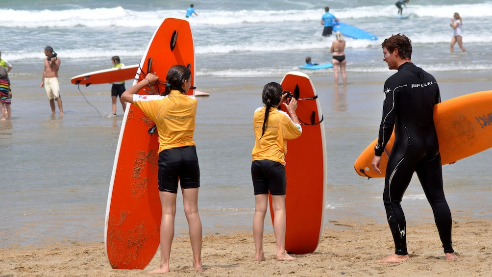 Charger l'élément 3 sur 5. Pair of girls and instructor with surfboards on the beach