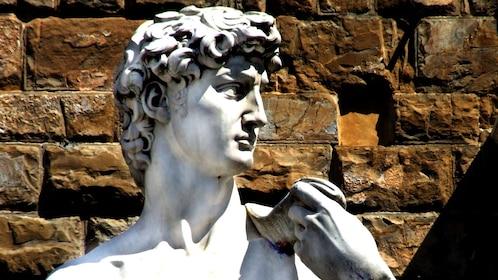 Outdoor sculpture of David next to brick wall