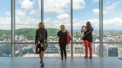 Three women look out at Montreal