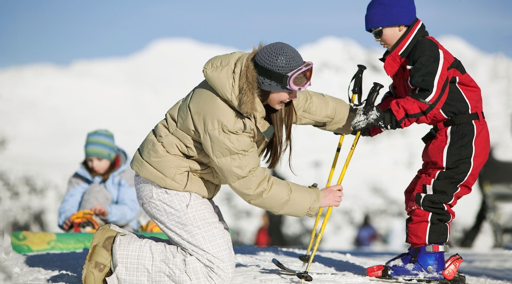 Mother helping her son with ski equipment in Aspen