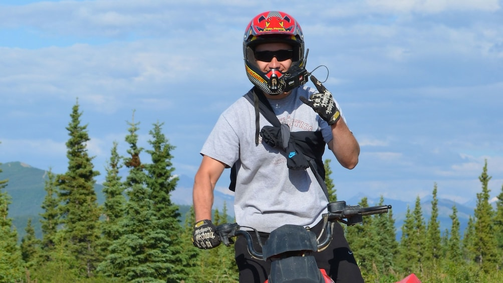 Show item 2 of 4. ATV rider with forest in the background in Denali National Park