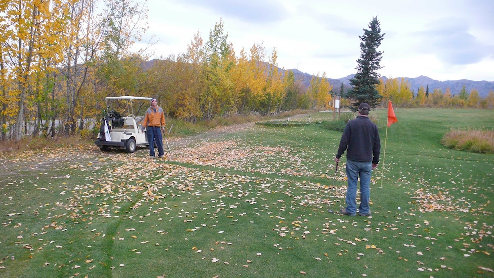 Show item 2 of 4. Two men playing golf in Alaska