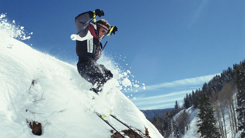 Show item 2 of 5. Skier goes off a jump on a mountain