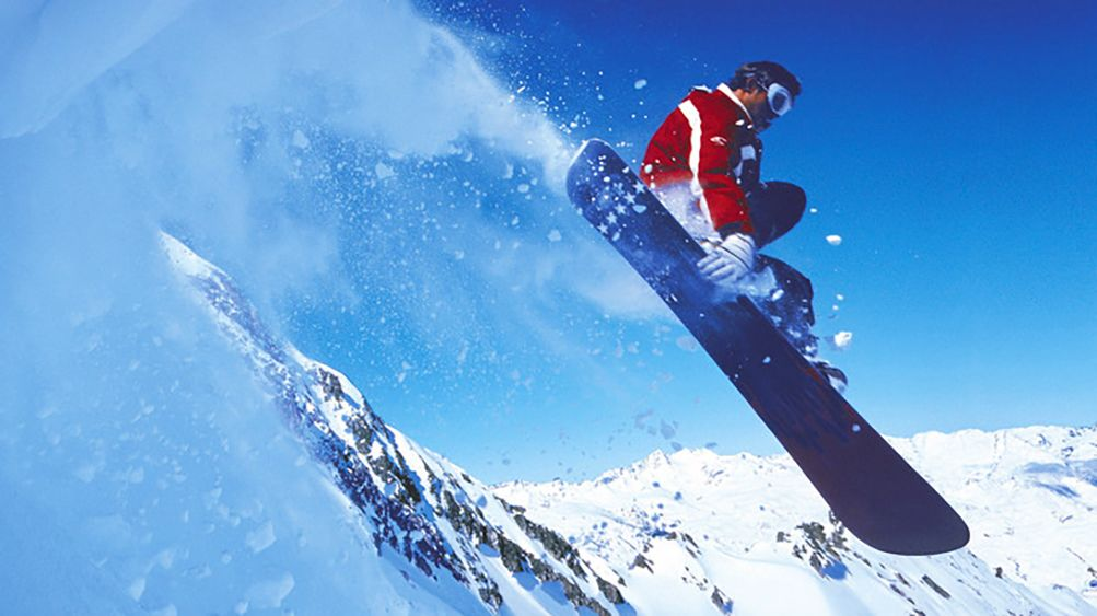 Snowboarder riding off a jump on a mountain top
