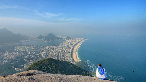 Woman perched on a mountain looking out at the coast in Rio de Janeiro