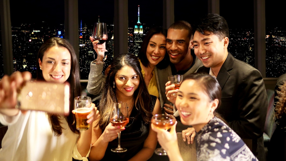 Show item 5 of 10. Group taking selfie during evening at One World Observatory in New York