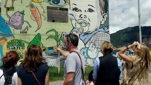Tourist looking at street art in Bogota