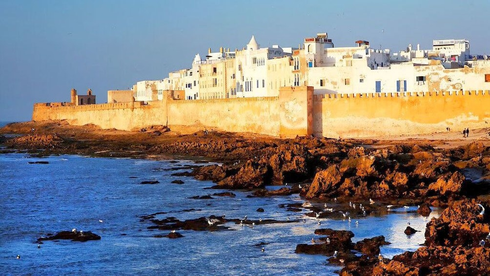 Charger l'élément 1 sur 5. View of the city behind the wall, rocky shoreline before the wall in Essaouira