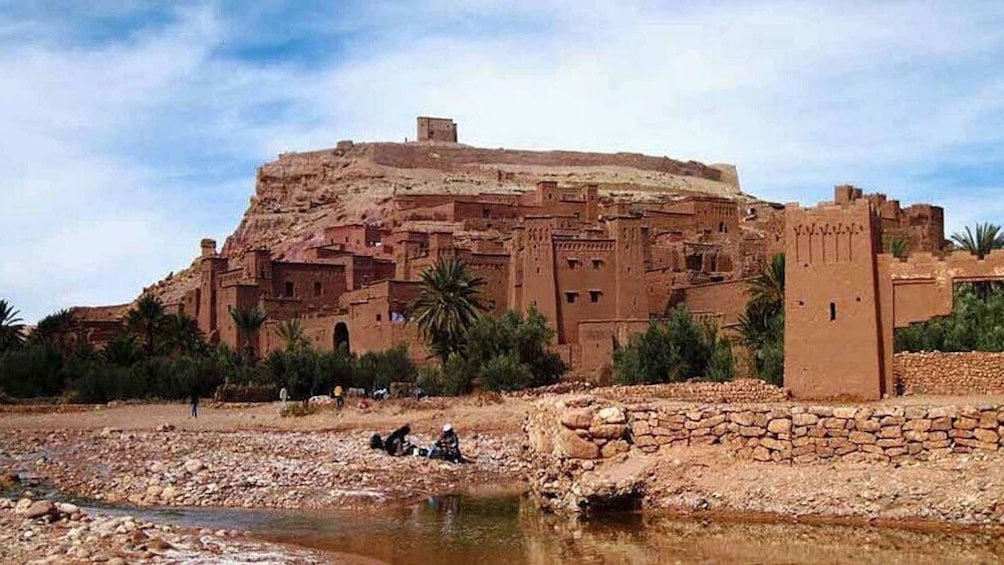 Charger l'élément 5 sur 5. View of city by the river, people sitting near river edge in Ait Ben Haddou Kasbah