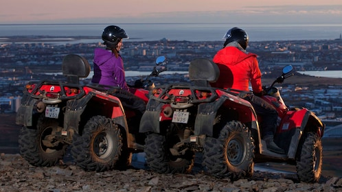 Two people riding an ATV at sunset
