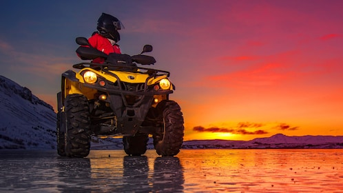 A person riding an ATV on a beach at sunset