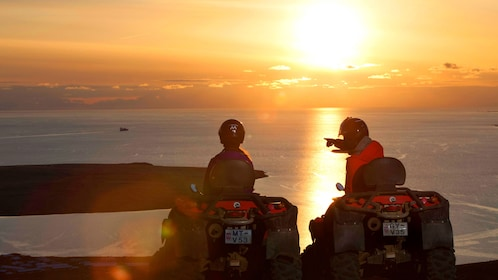 Two people on ATVs with a sunset