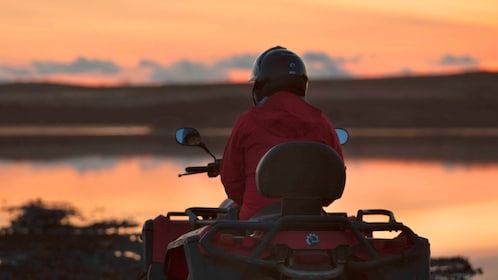 Person riding an ATV at sunset