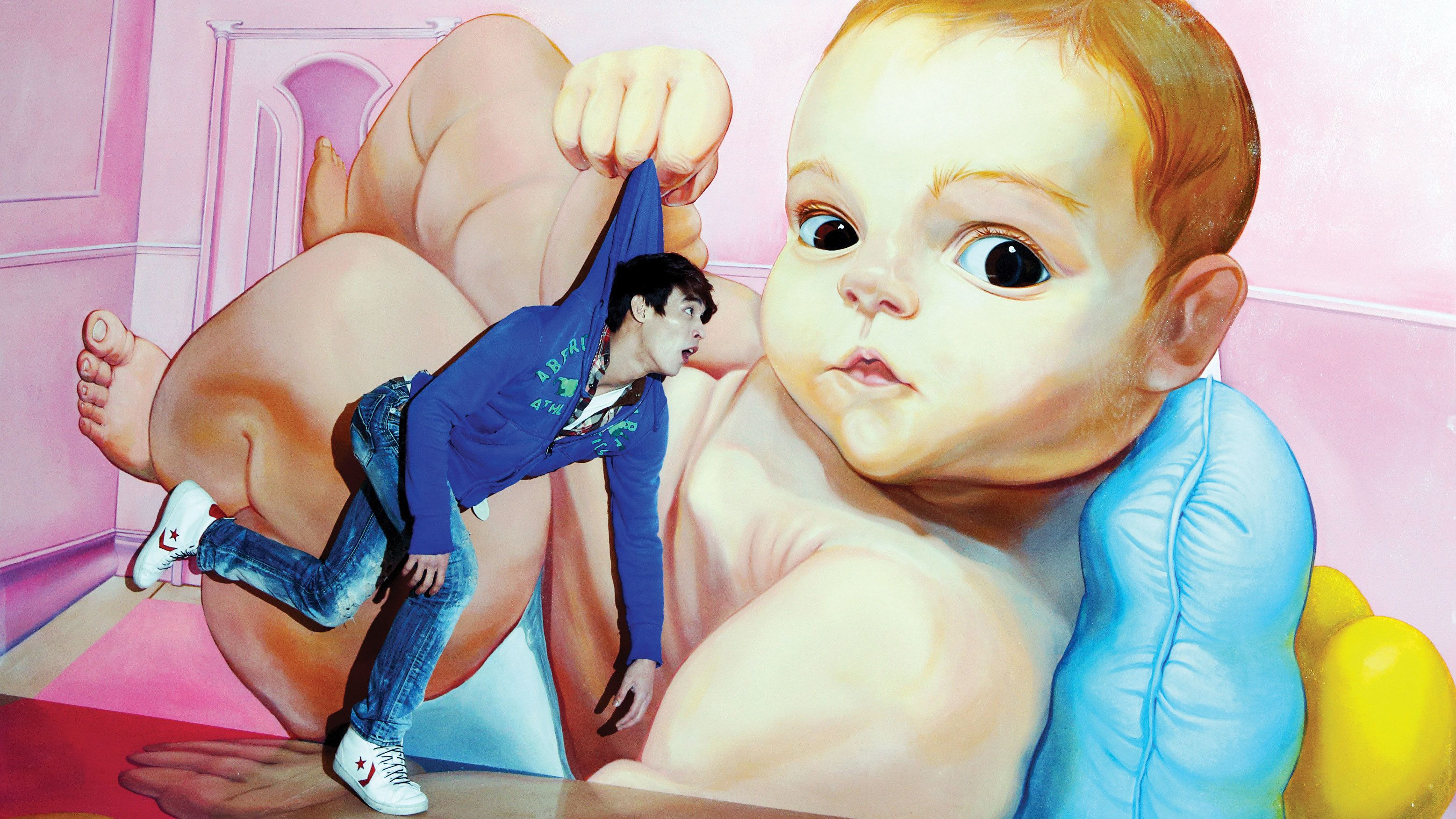 Man posing as being picked up by large painting of baby at Trick Eye Museum in Singapore