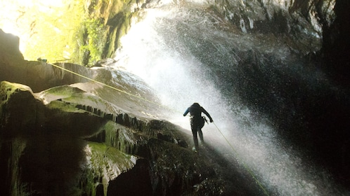 Person climbing down a waterfall in in Kawarau Canyon