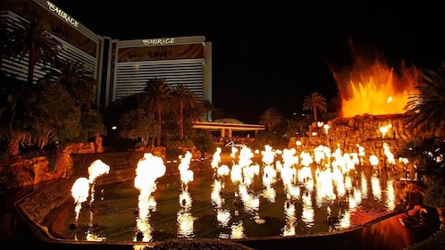 View of display pool in front of hotel with multiple flames throughout the pool at night in Las Vegas