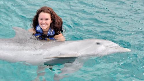 Young woman enjoying a dolphin encounter on the Cozumel Dolphin Swim Adventure