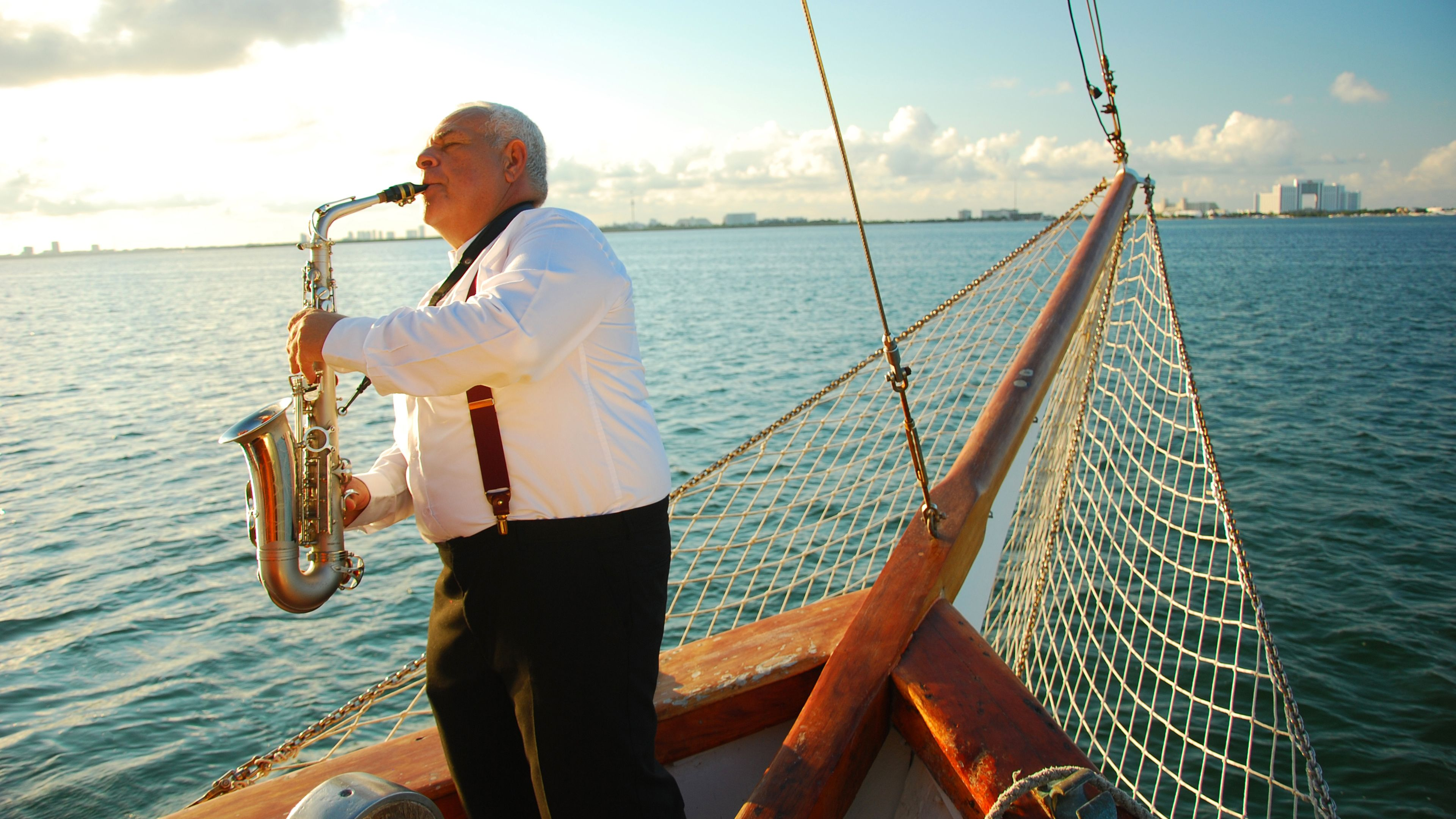 Old Man playing a saxophone on a boat in Mexico