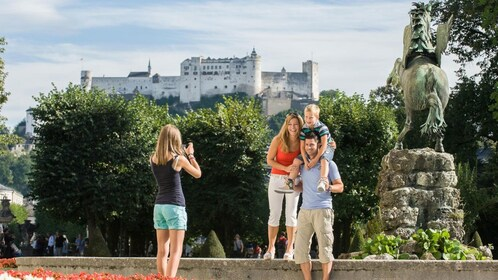 Family taking a photo next to a statue in Salzburg