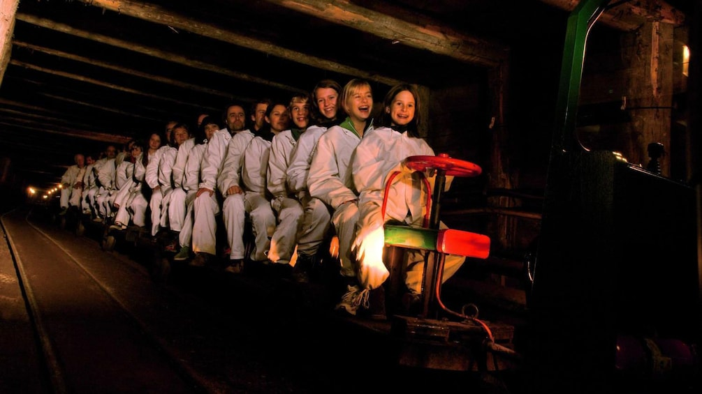 Show item 2 of 5. Tourists embark on a trolley ride through the salt mine