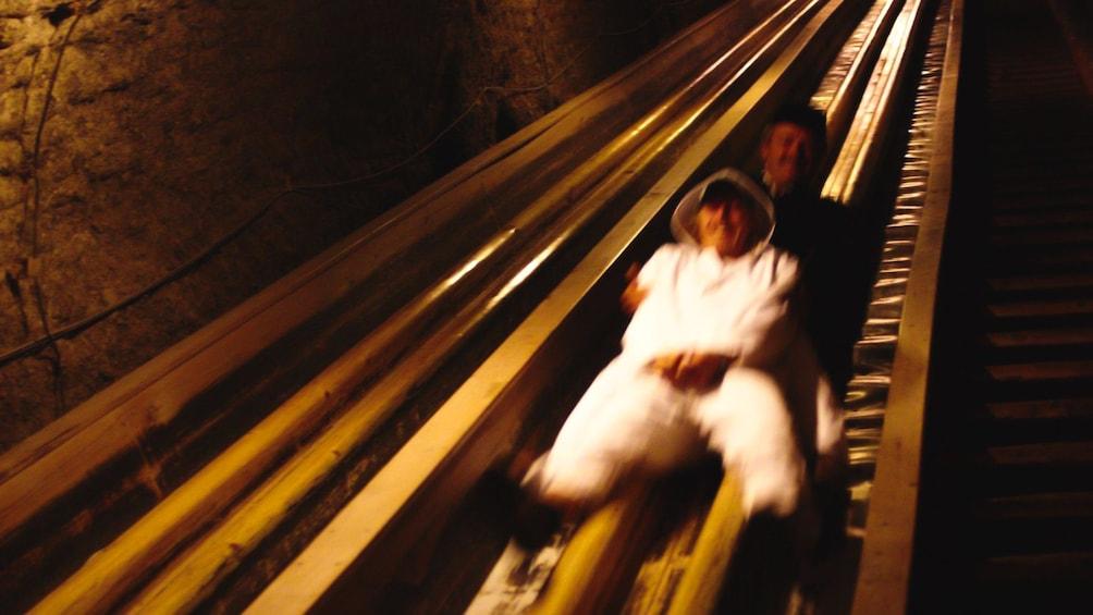 Foto 3 von 5 laden Two people sliding down giant slide in salt mines.