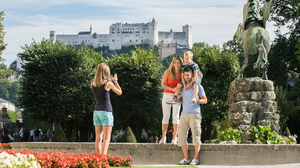 Show item 4 of 5. Family photo at a statue with castle a hill in the background in Salzburg