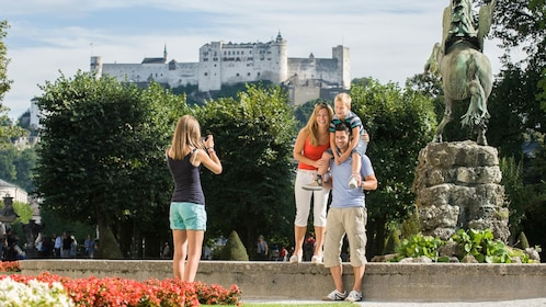 Family photo at a statue with castle a hill in the background in Salzburg