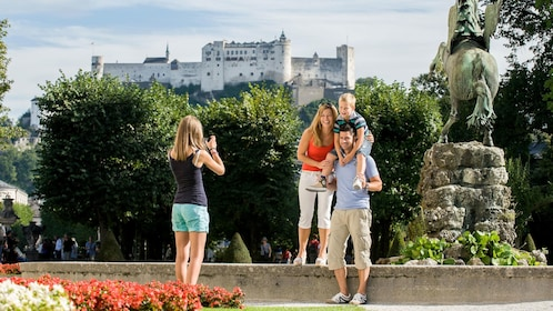 Family photo at a statue with hilltop castle in the background in Salzburg