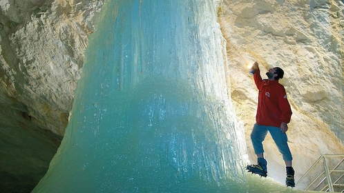 Man looking at ice formation in a cave in Austria